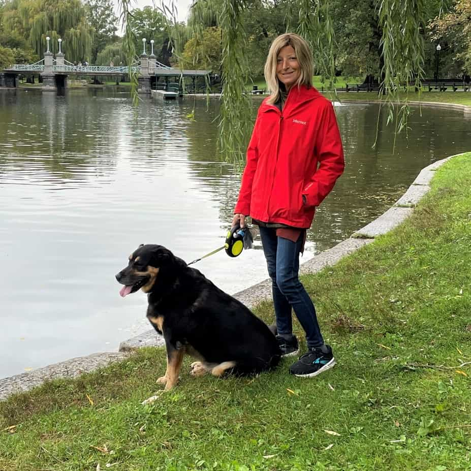A woman and her leashed dog standing on grass near a small body of water