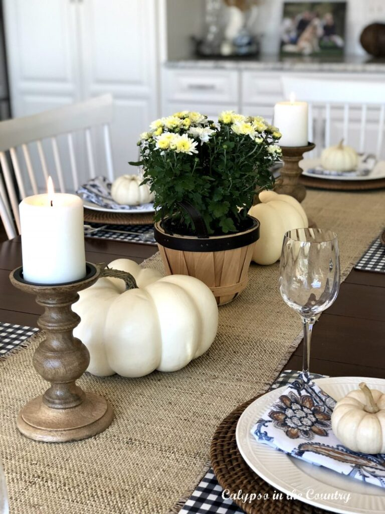 a table dressed with a white pumpkins a brown table runner and rustic candlesticks with white candles